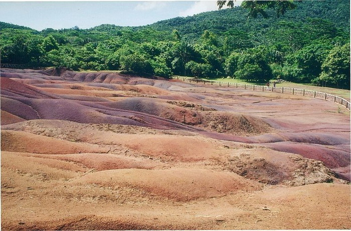 Разноцветные дюны ограждены небольшим деревянным забором