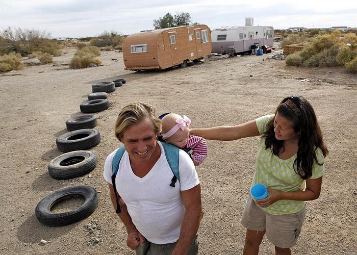 Счастливая молодая семья рядом со своим вагончиком в Городе бетонных плит