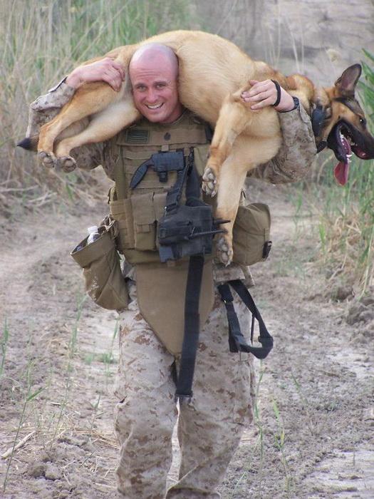Солдат несет своего четверолапого напарника на базу после двухчасовой тренировки