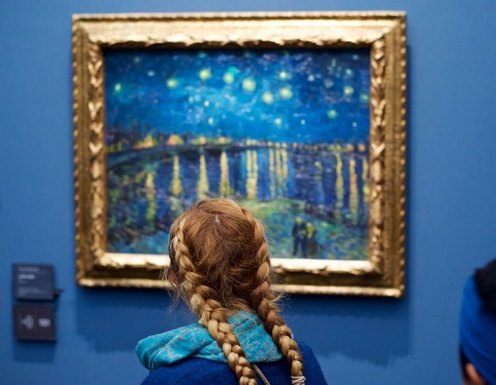 Девушка рассматривает полотно Ван Гога *Звездная ночь над Роной*.