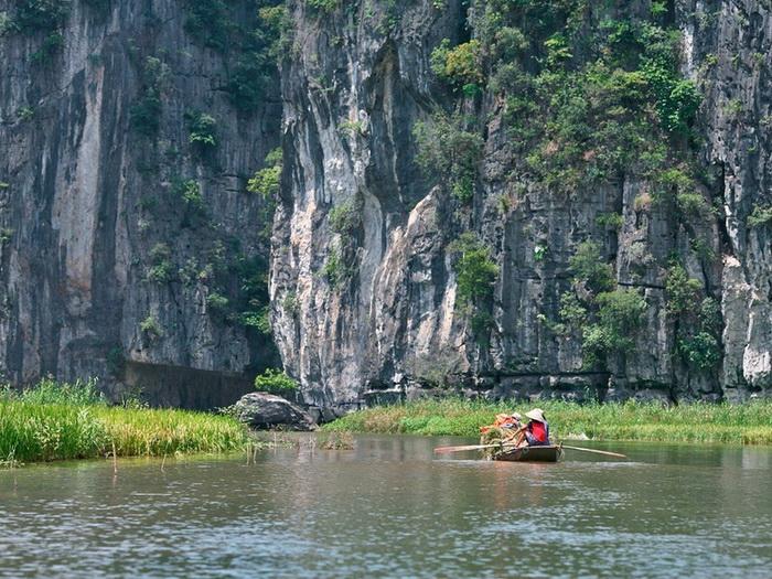 Прогулка по реке Ngo Dong проходит вдоль отвесных скал