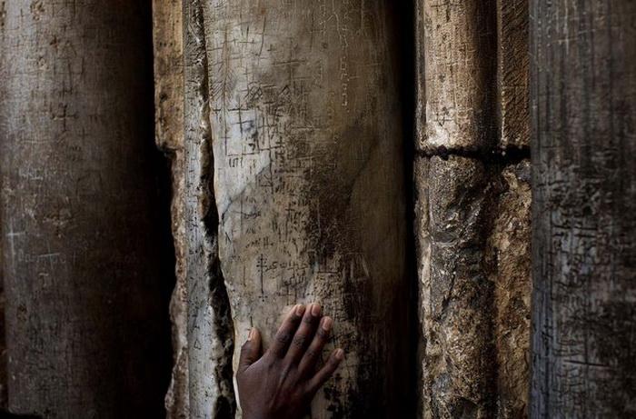 Христианский паломник дотрагивается до столба в Храме Гроба Господня