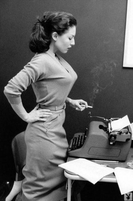Красивая секретарша в облегающем платье с тонким ремешком на талии.