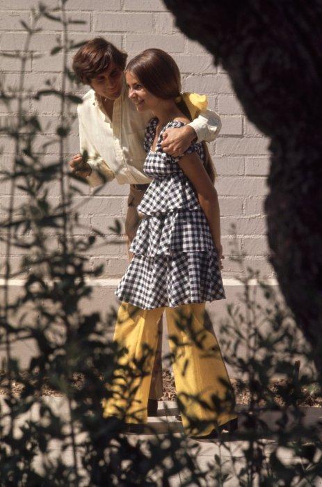Девушка в клетчатой блузе с воланами и молодой человек с бакенбардами.