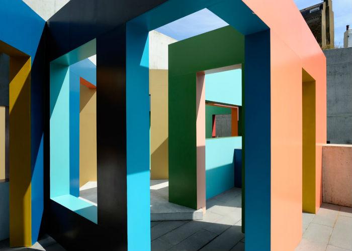 Деревянные поверхности инсталляции окрашены в яркие, жизнеутверждающие цвета, которые отсылают зрителей к традиционным приморским павильонам и пляжным хижинам