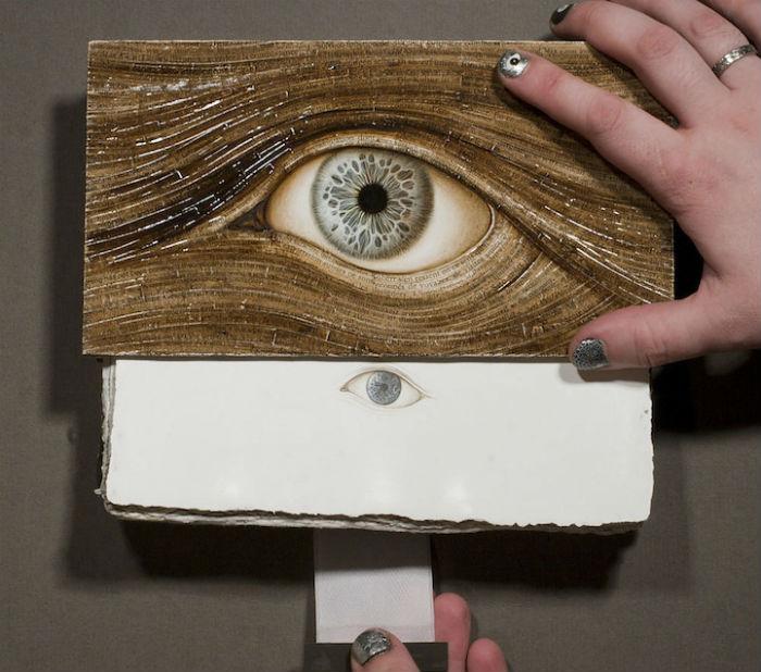 Используя акварель, акрил и сусальное золото, художник украшает книги витиеватыми изображениями человеческого глаза