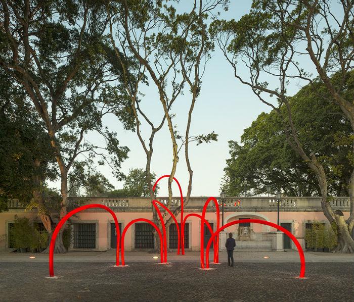 «Сети» из смежных красных арок будто бы опутывают пышные зелёные кустарники, ловко огибают деревья и легко перебираются через каменную ограду дворцового парка