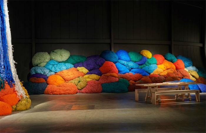 Десятки крупных ярко окрашенных «валунов» из цветных нитей хаотично расположены вдоль стен арт-пространства