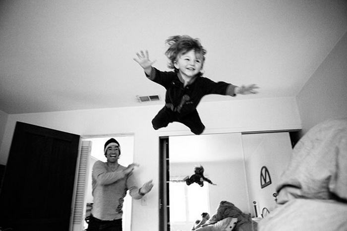 Отец бросает сына на кровать