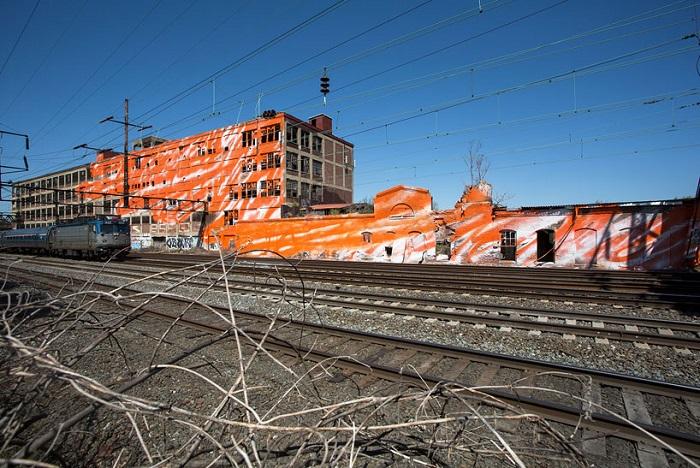 Оранжевое здание возле железной дороги.