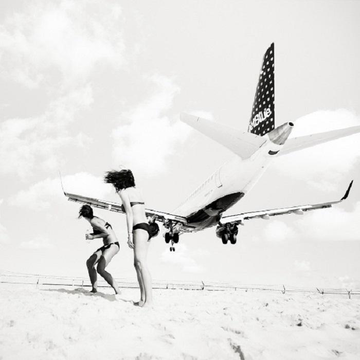 Самолет летит низко над пляжем.
