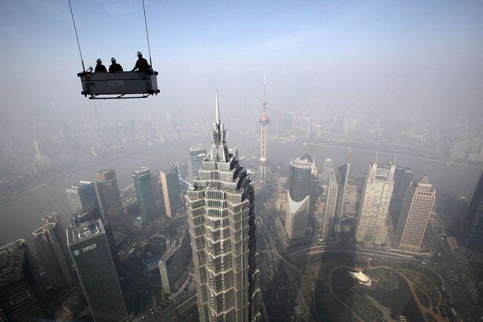 Рабочие по чистке окон у здания Шанхайского всемирного финансового центра