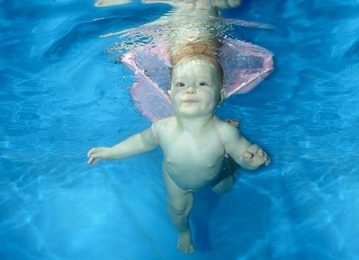 Младенец учится плавать