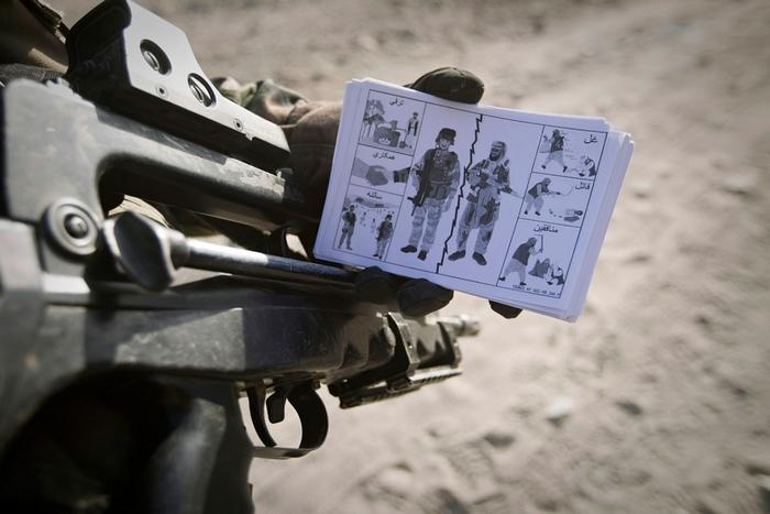 Солдат с брошюркой для местных жителей с изображением разницы между солдатами и боевиками.