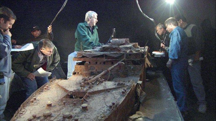 Джеймс Кэмерон и его команда изучают маршрут будущих подводных съемок на макете останков Титаника.