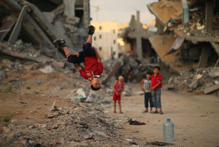 Мальчишки демонстрируют мастерство паркура в окружении разрушенных зданий Газа.