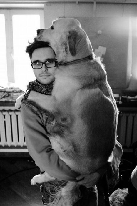 Черно-белый снимок хозяина с собакой на руках.