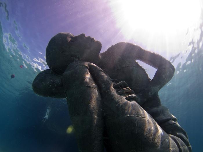 Гигантская подводная скульптура девушки на дней океана.