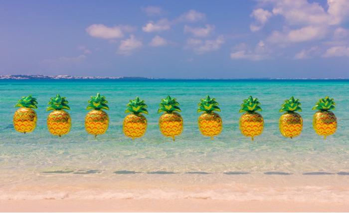 Веселые ананасы на фоне лазурного берега.