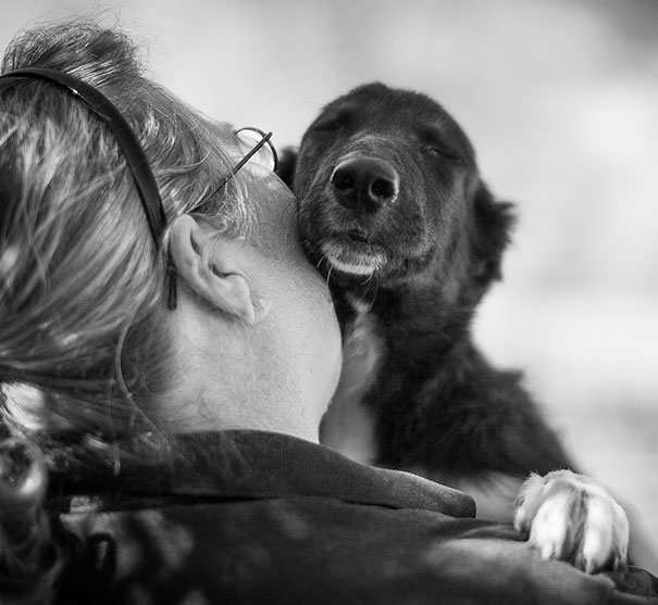 Черно-белый снимок женщины со щенком.