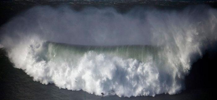 Противостояние серфингиста бушующим водам океана.