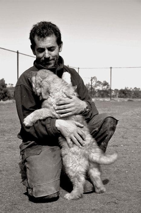 Черно-белая фотография щенка и его хозяина.