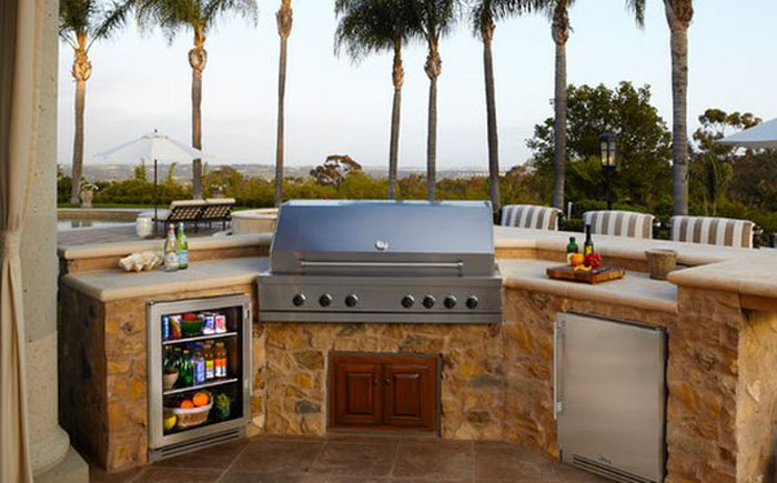 Небольшая кухня на открытом воздухе в комплекте со встроенной холодильной камерой.