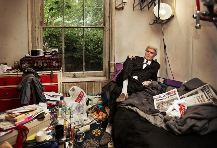 Джордж в элегантном костюме, окруженный привычным ему беспорядком.