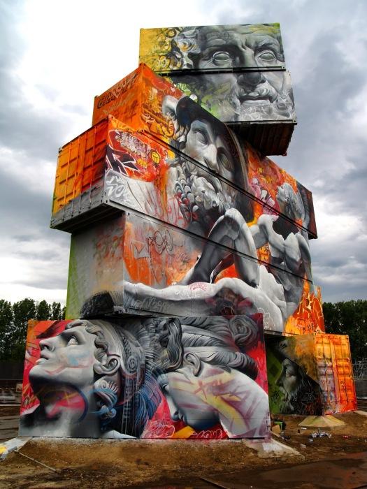 Граффити от испанского дуэта на скульптуре из транспортных тар.