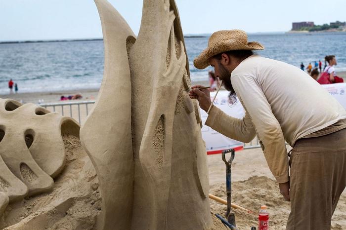 Скульптор создает свой шедевр из песка.