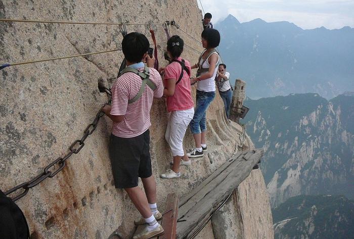 Туристы перемещаются по тонким, узким дощечкам на отвесной скале.