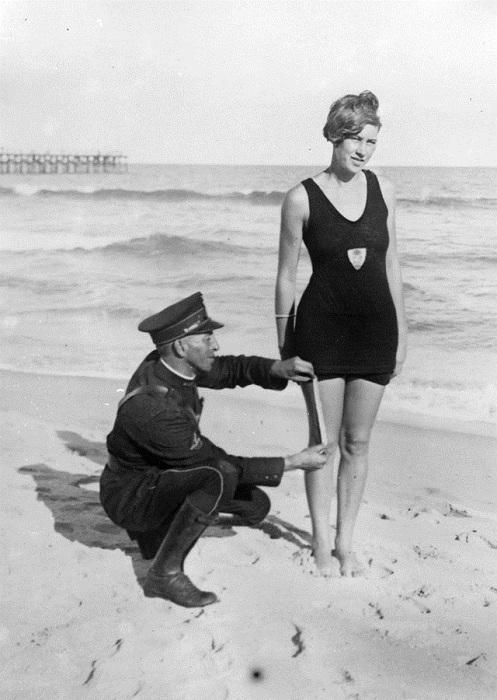 На пляже блюститель порядка измеряет даме длину купальника.
