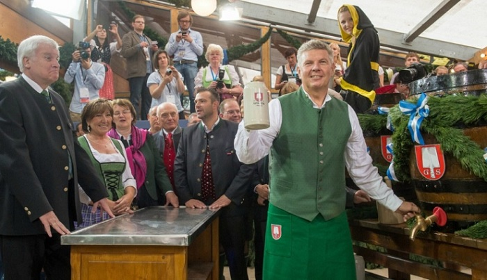 Мэр Мюнхена откупоривает бочку с пивом.