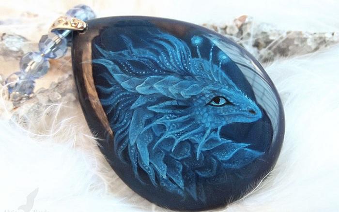 Поклонница фэнтези рисует драконов на поделочных камнях.