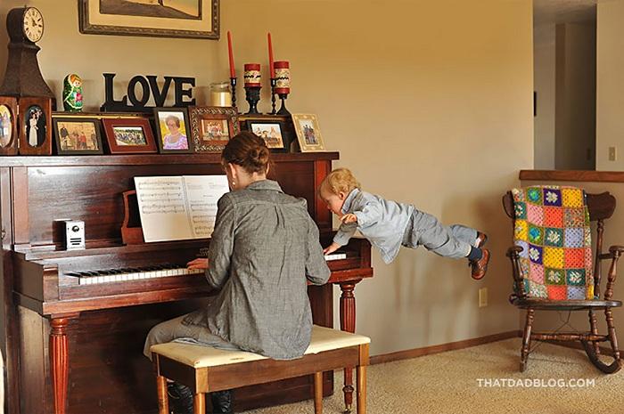 Отец фотографирует сына с синдромом Дауна летающим.