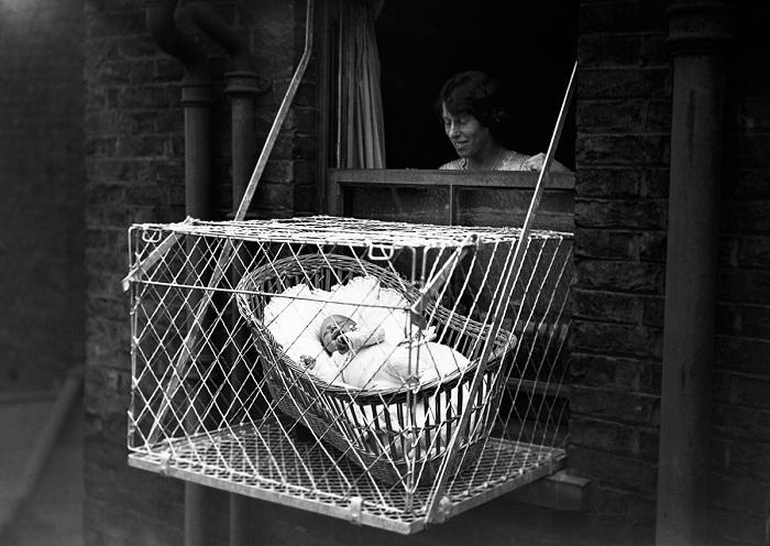 Американка начала 20 века заботится о малыше, выставляя люльку за окно многоэтажки.