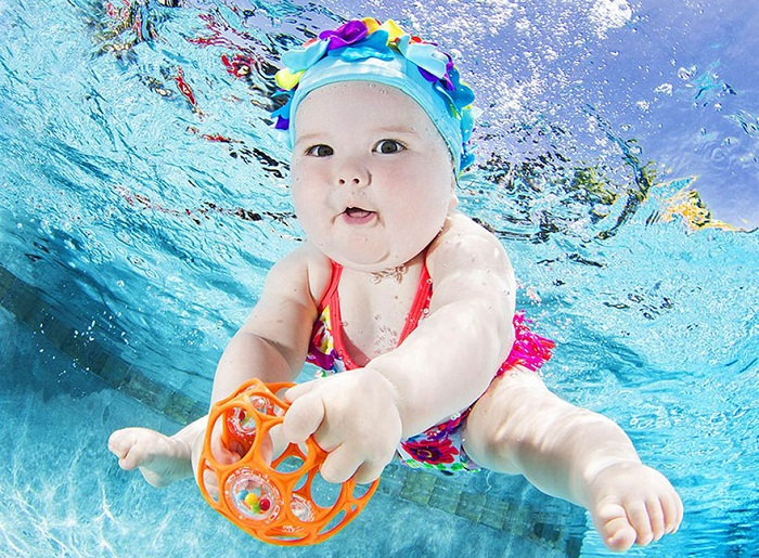 Малышка, которая учится плавать под водой.