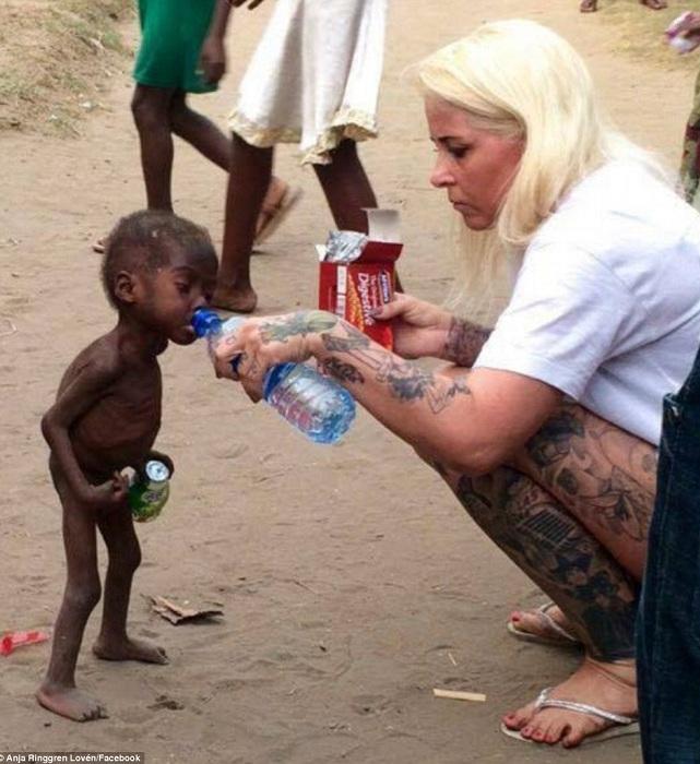 Волонтер Anja Ringgren Loven дает истощенному мальчику попить.