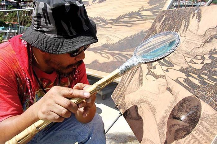 Художник выжигает работу при помощи солнечного света.