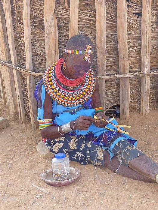 Африканская женщина плетет сувениры из бисера.