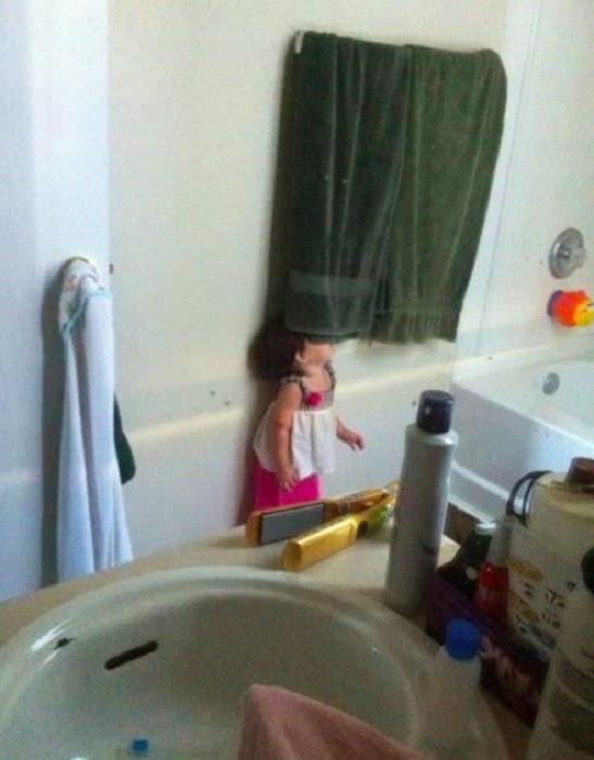 Малышка пытается частично спрятаться под полотенцем.