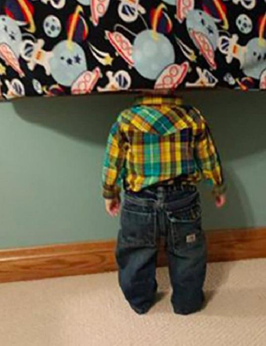 Мальчик прячется, отвернувшись лицом к стеной.