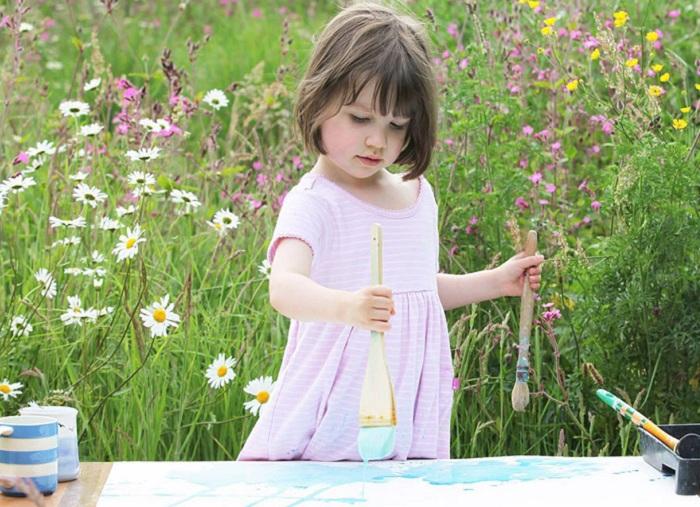 5-летняя девочка рисует красивые картины.