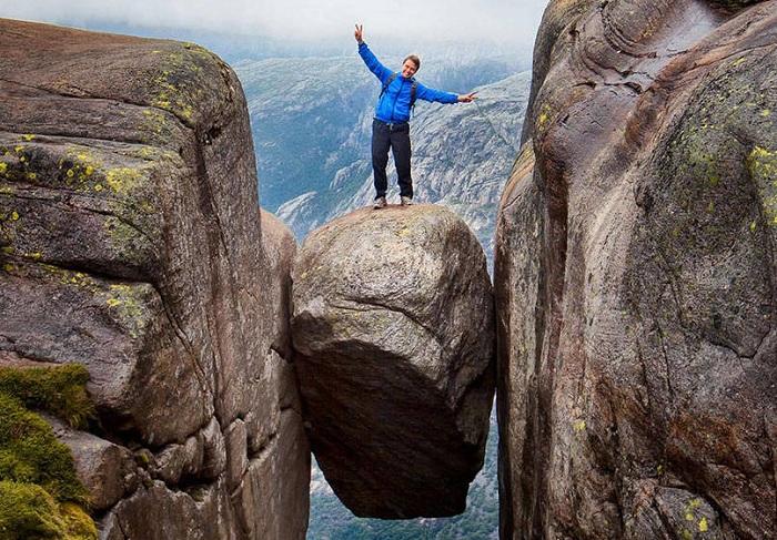 Валун Kjeragbolten в Норвегии - любимое место для фотографирования отчаянных туристов.
