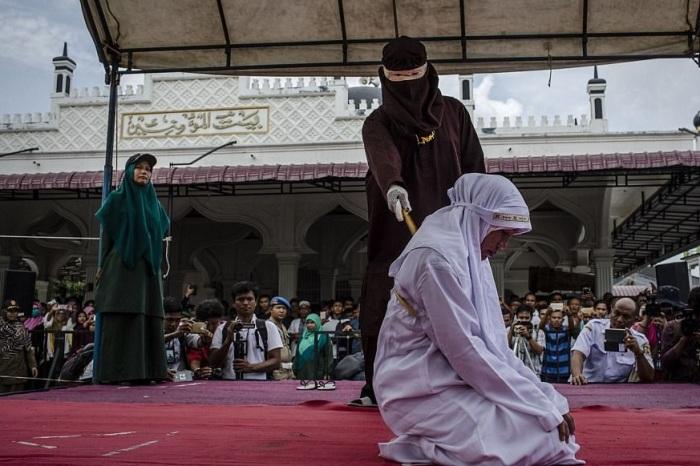 Наказание исполняет палач в маске. | Фото: dailymail.co.uk.