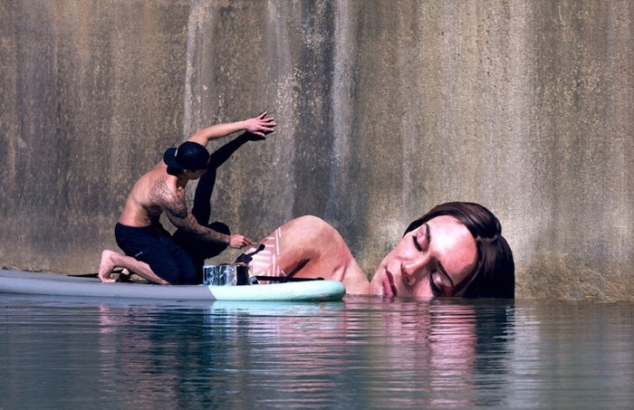 Художник рисует портреты, сидя на доске для серфинга.