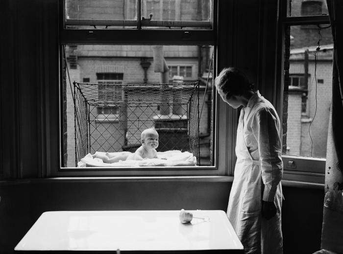 Ретро-фото детей в клетках, подвешенных за окнами домов.