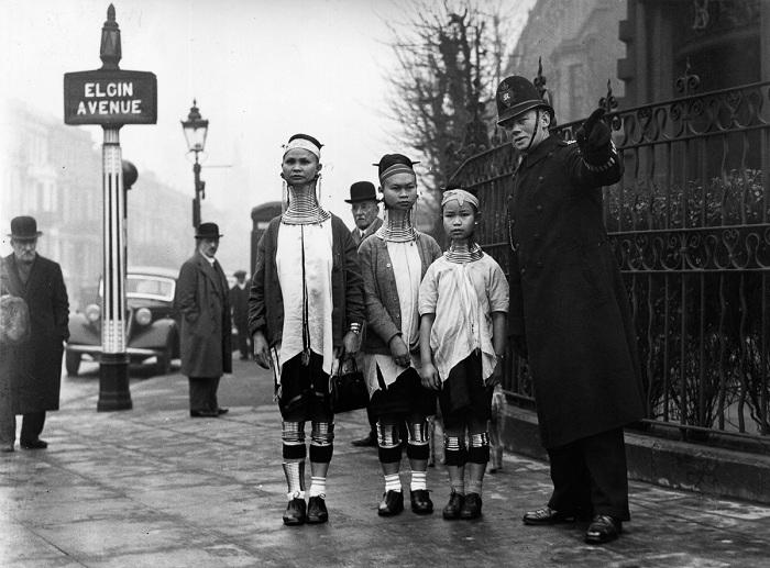 Полисмен указывает женщинам с длинными шеями путь.
