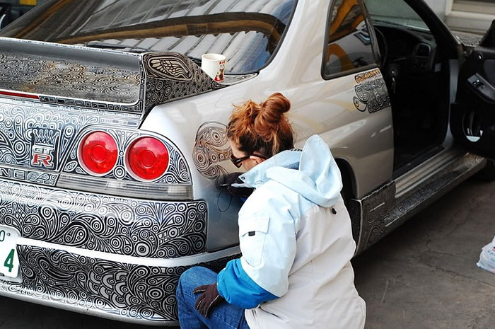 Жена полностью разрисовывает автомобиль мужа.
