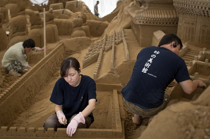Работа над созданием скульптур из песка.